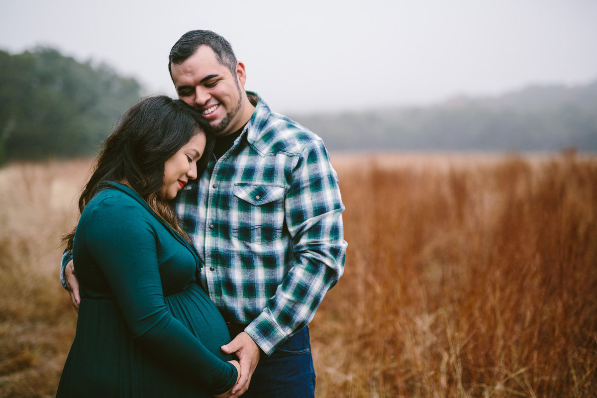 Expecting couple holding her belly standing in field at in San Antonio park.