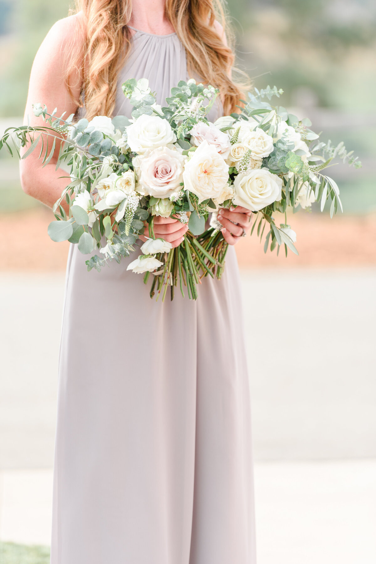 bridesmaid holding a full bouquet of flowers