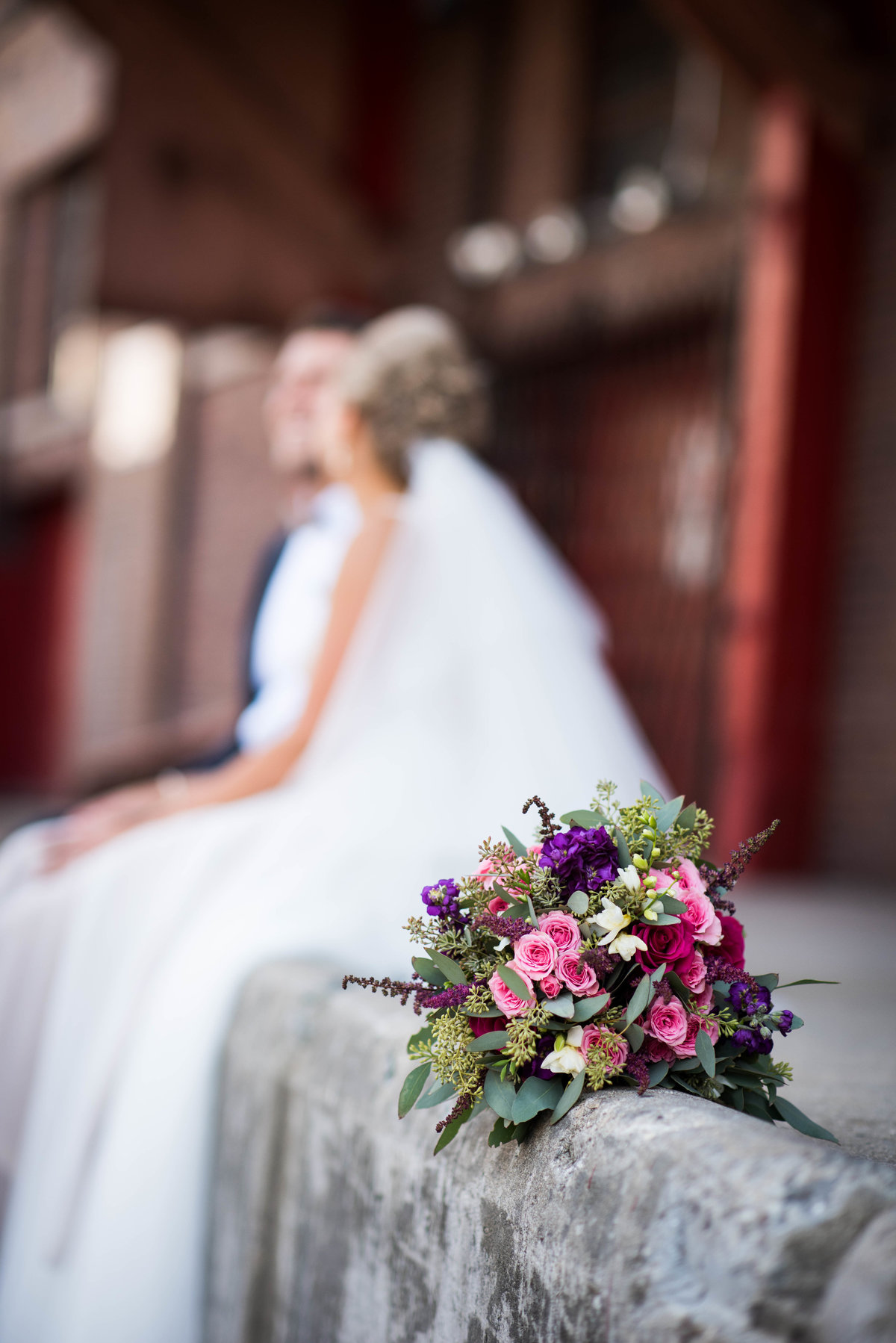 Wedding bouquet, couple in background, Chicago IL.