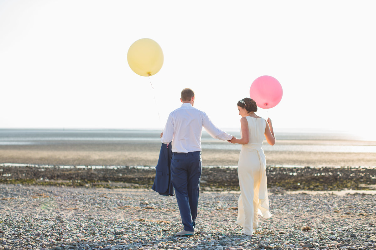 bride and groom on beach with big balloons