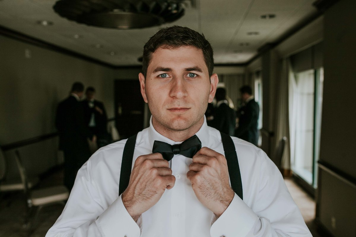 Groom straightens bow tie at Omni Severin ball room