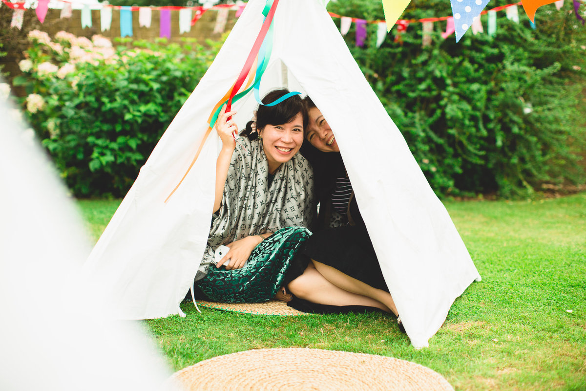 guests in a mini tipi with bunting at this boho wedding