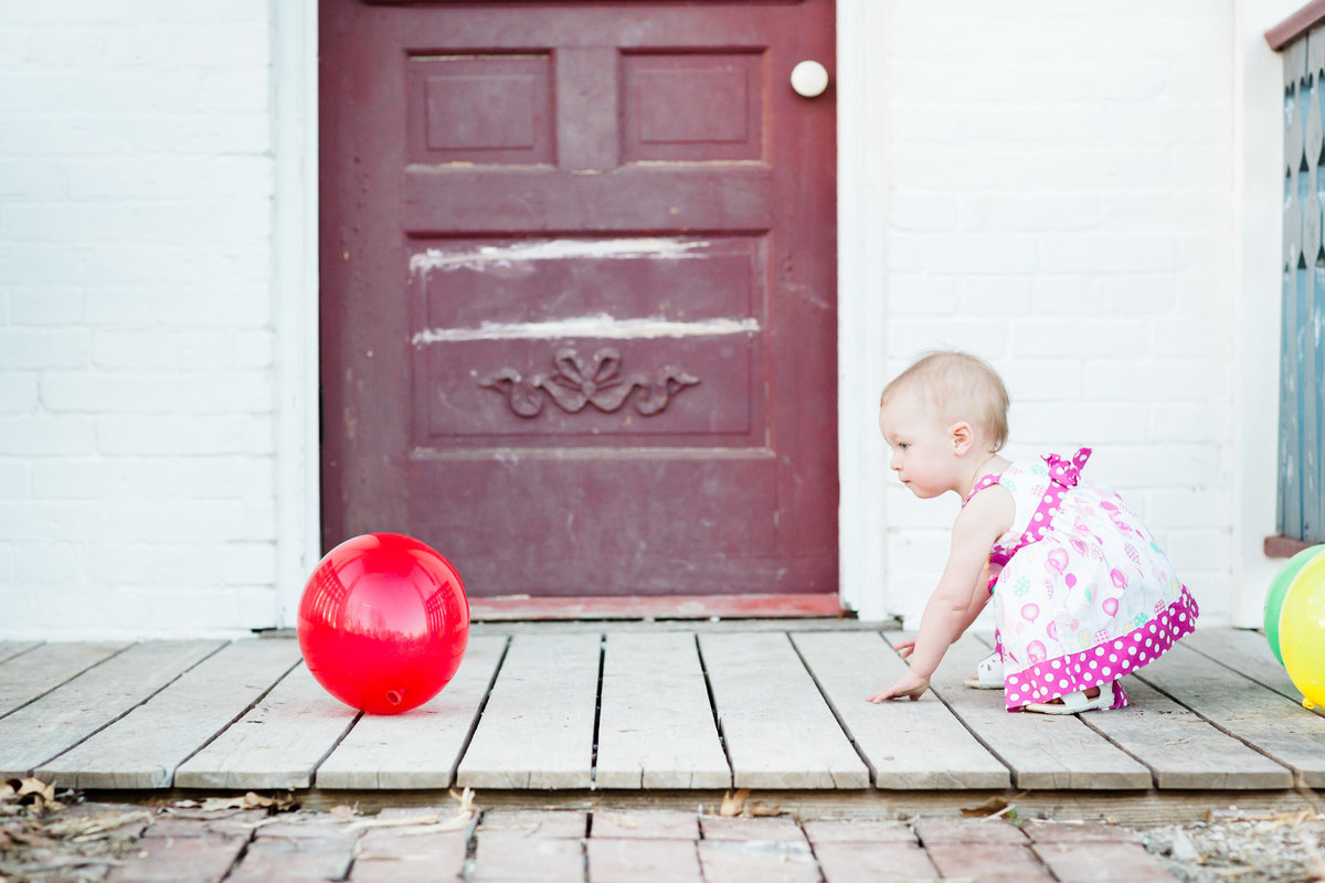 baby chasing red ballon during cake smash session
