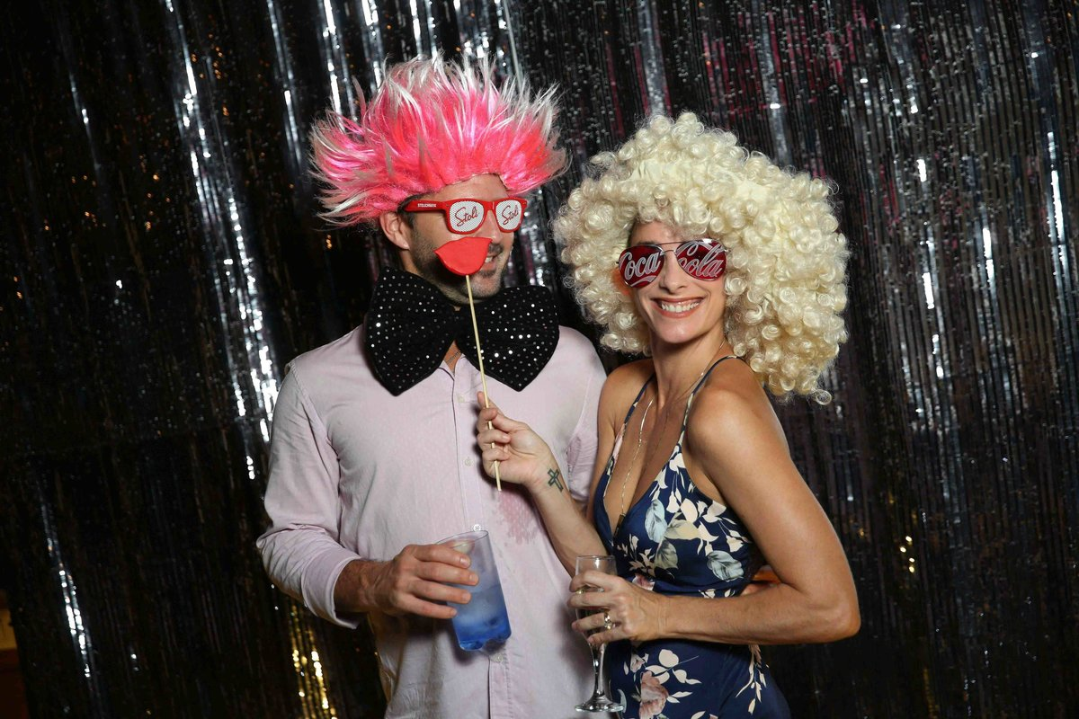 Couple has fun with wigs, glasses, and a hug bow tie. Photobooth by Ross Photography, Trinidad, W.I..