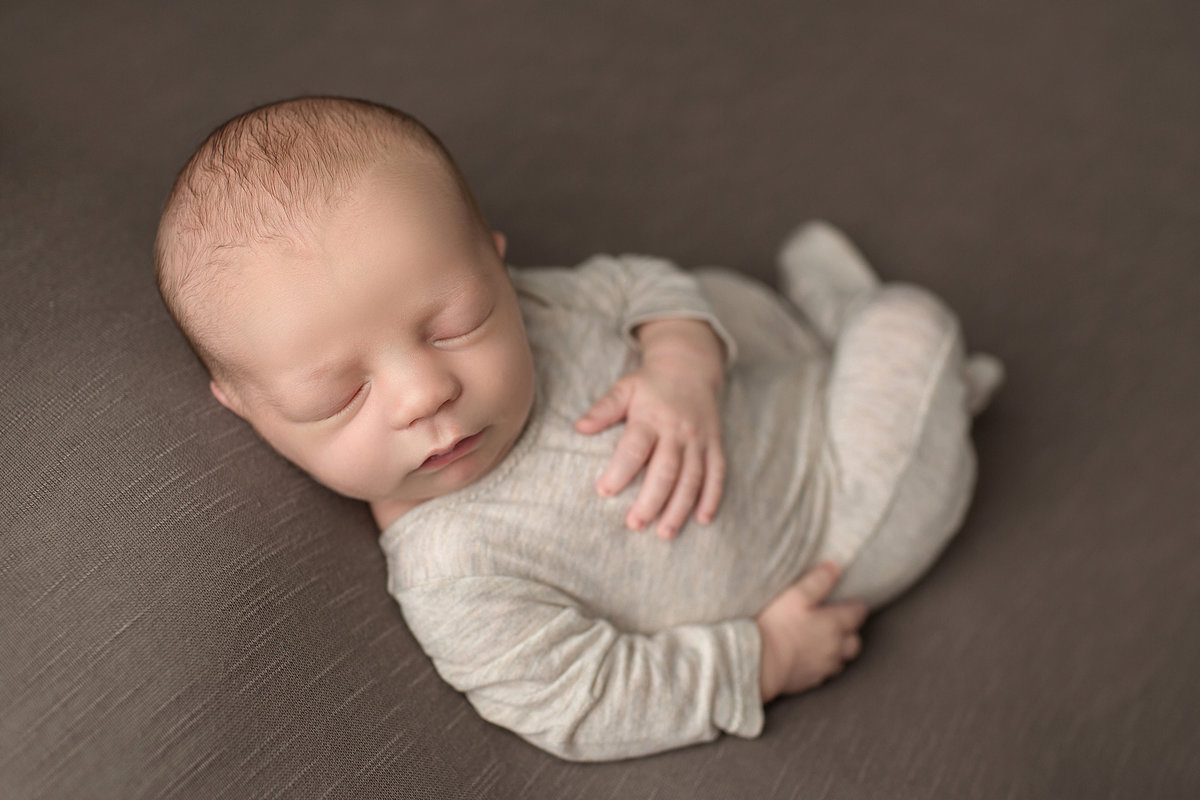 PA newborn in cream outfit asleep on brown blanket posed on back