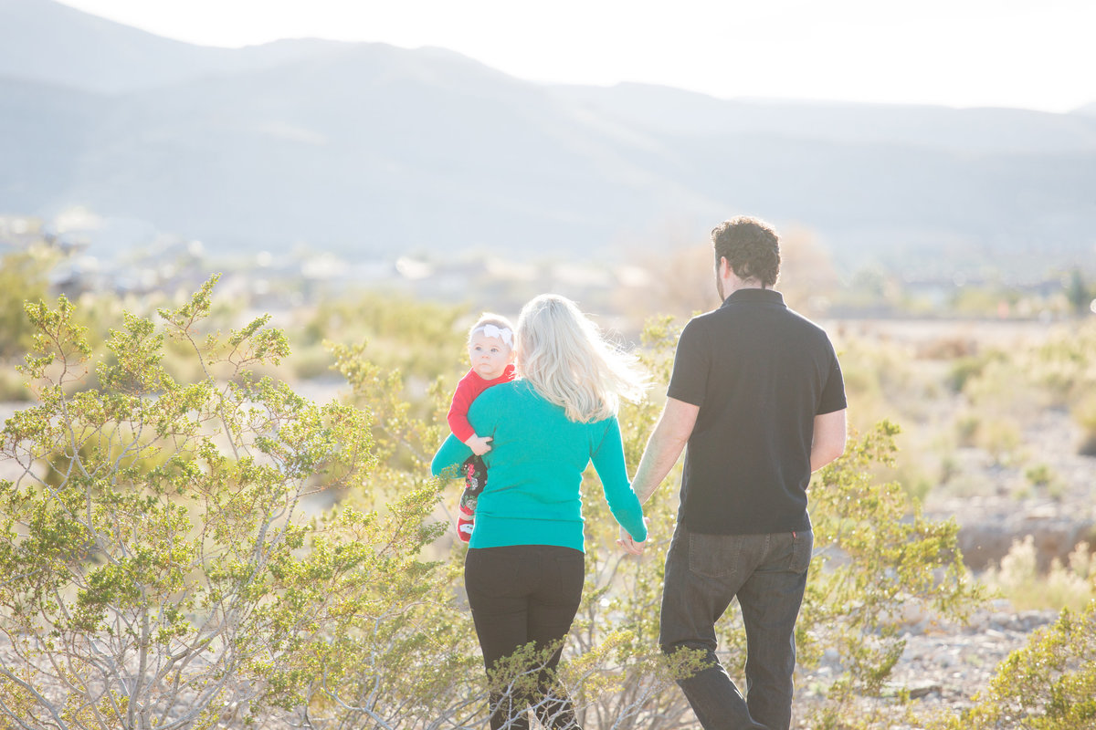 family walks through las vegas desert for family photo at golden hour