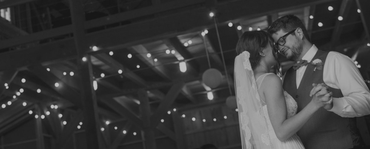 Bride and grooms first dance in a barn lit with twinkle lights