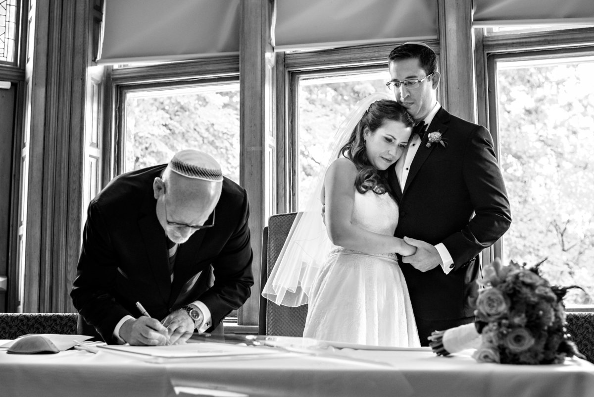 A jewish wedding couple watch as their rabbi signs the ketubah before the ceremony at Temple Beth Hillel.