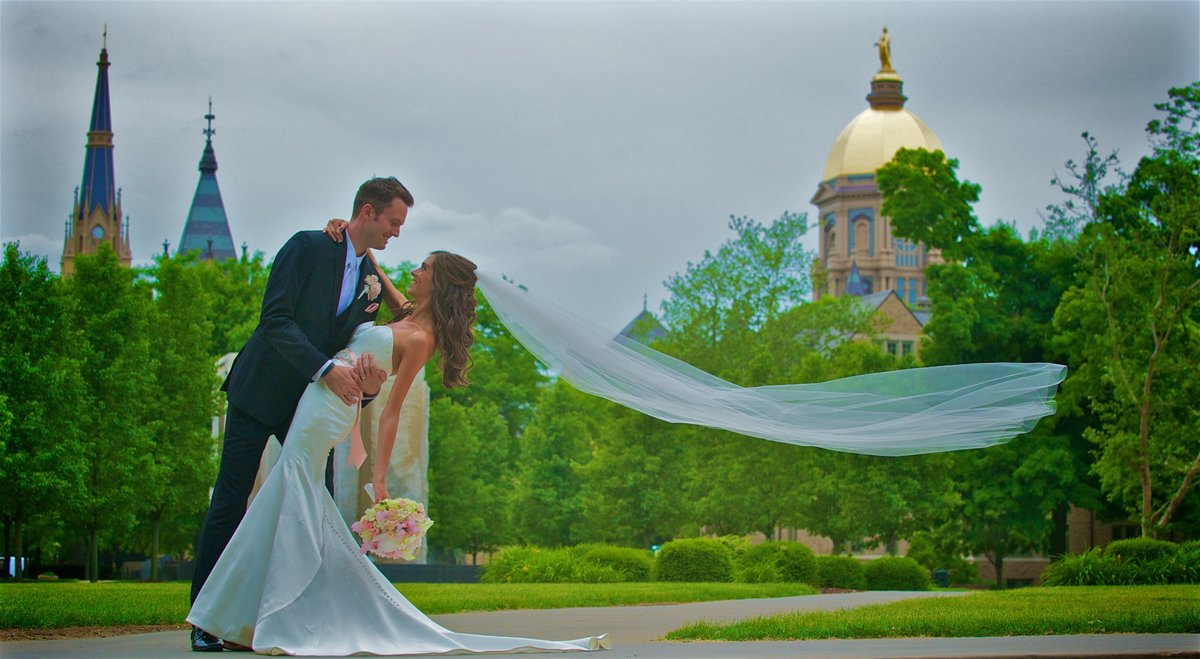 The wind catches the Bride's veil in between the Golden Dome and Basilica of the Sacred Heart