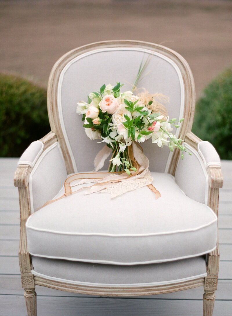 chair with peach ant white bride bouquet