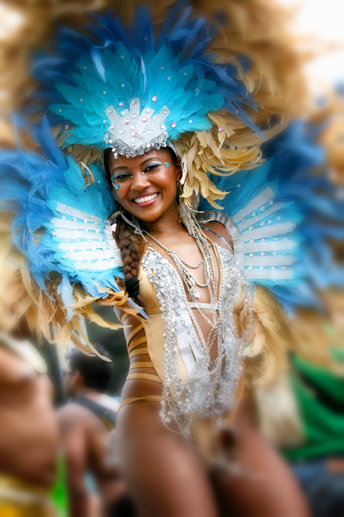 A female masquerader smiles in her beige and blue feathered costume. Photo by Ross Photography, Trinidad, W.I..