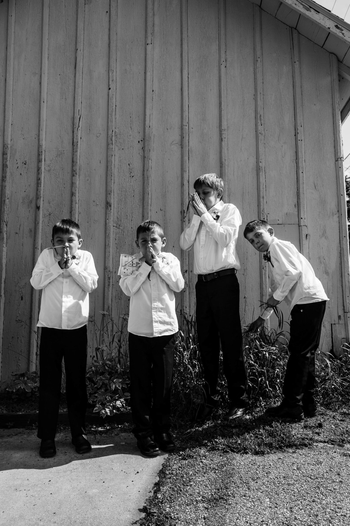 four boys blowing grass blades behind church after wedding