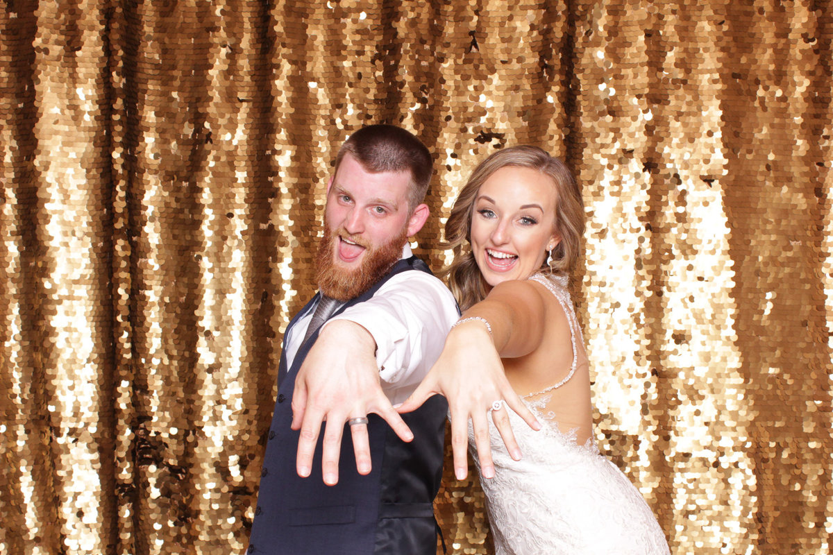 Bride and groom pose for a pic in front of a gold sequin backdrop at their wedding reception