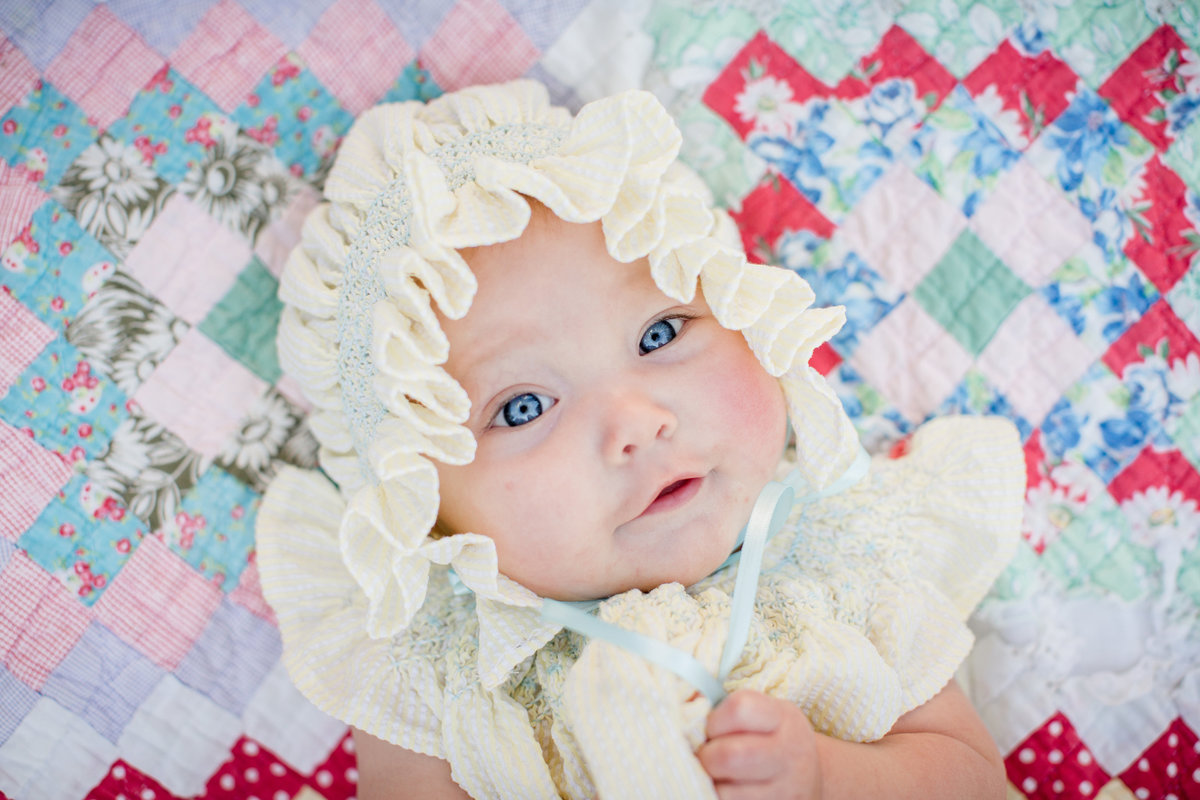 Little girl in a bonnet looking up at the camera on a quilt  by Knoxville Wedding Photographer, Amanda May Photos.