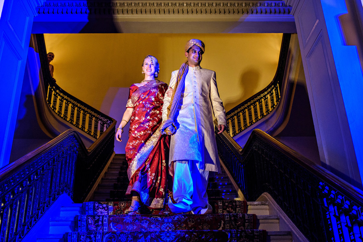 An indian wedding couple walk down the staircase to their reception at the Racquet Club of Philadelphia.
