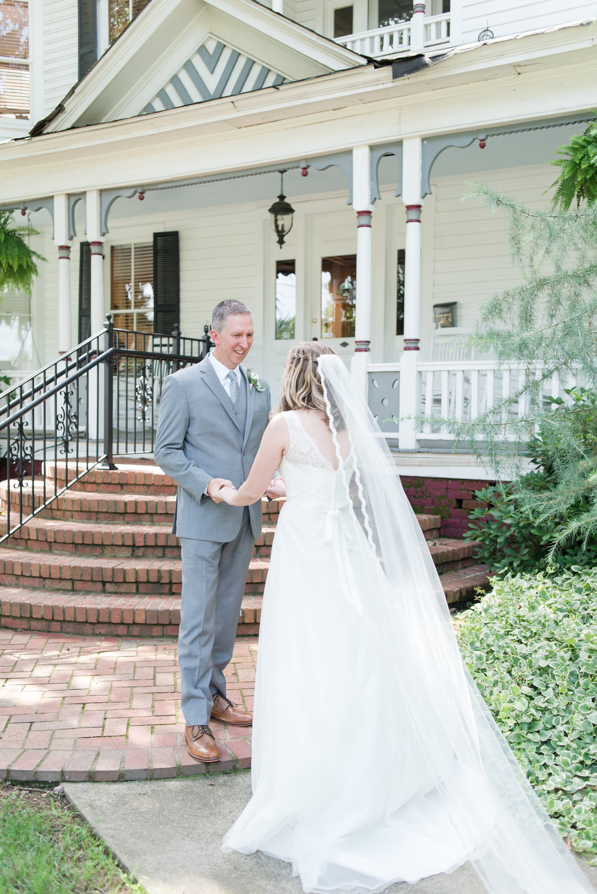 a bride having a first look with the father of the bride in front of  the house at Gardens at Gray Gables in Summerfield NC