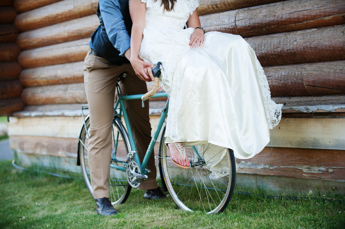 bride rides bicycle handles in wedding dress at cooper spur