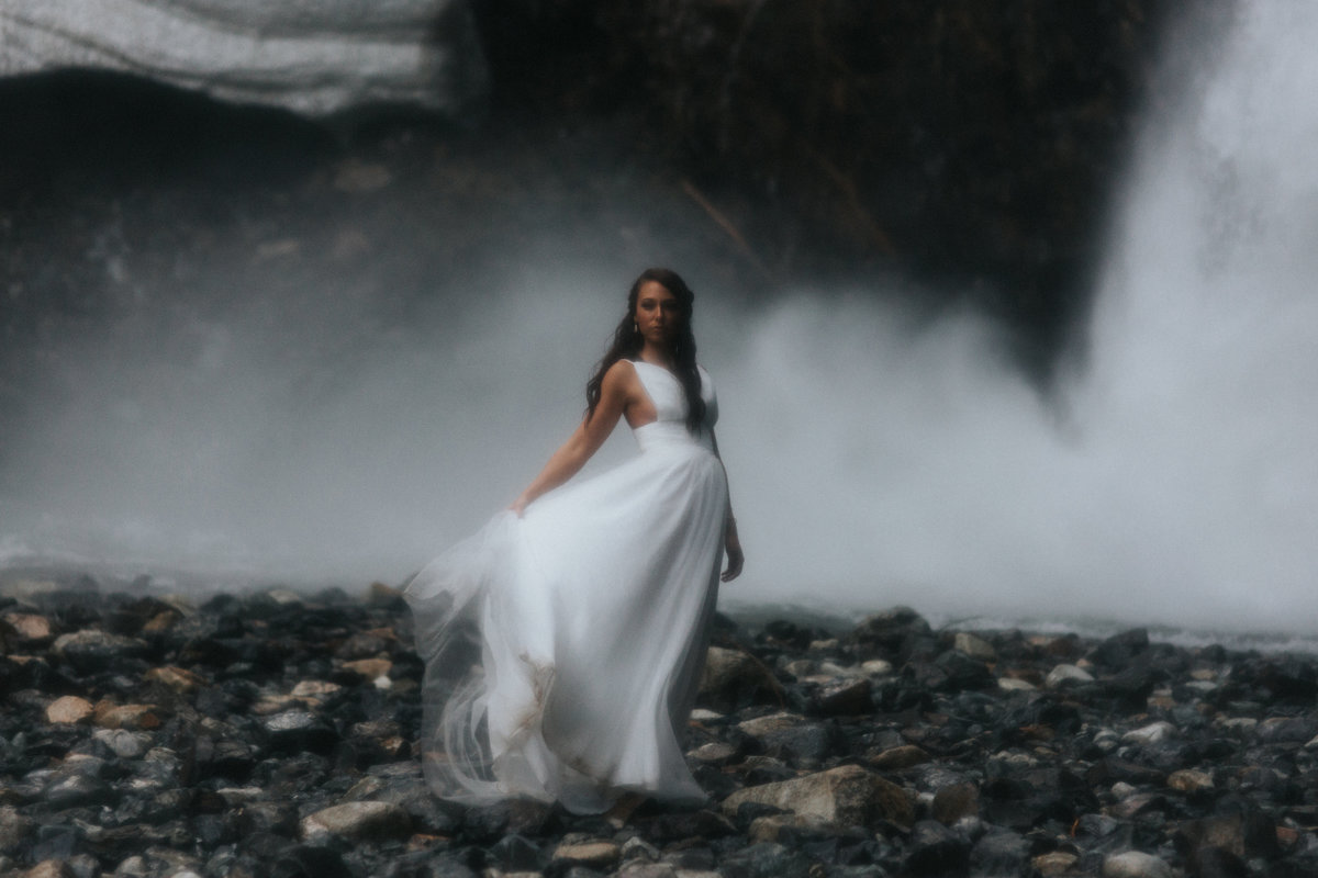Portrait of a bride under a waterfall during her elopement outside of Seattle, Washington.