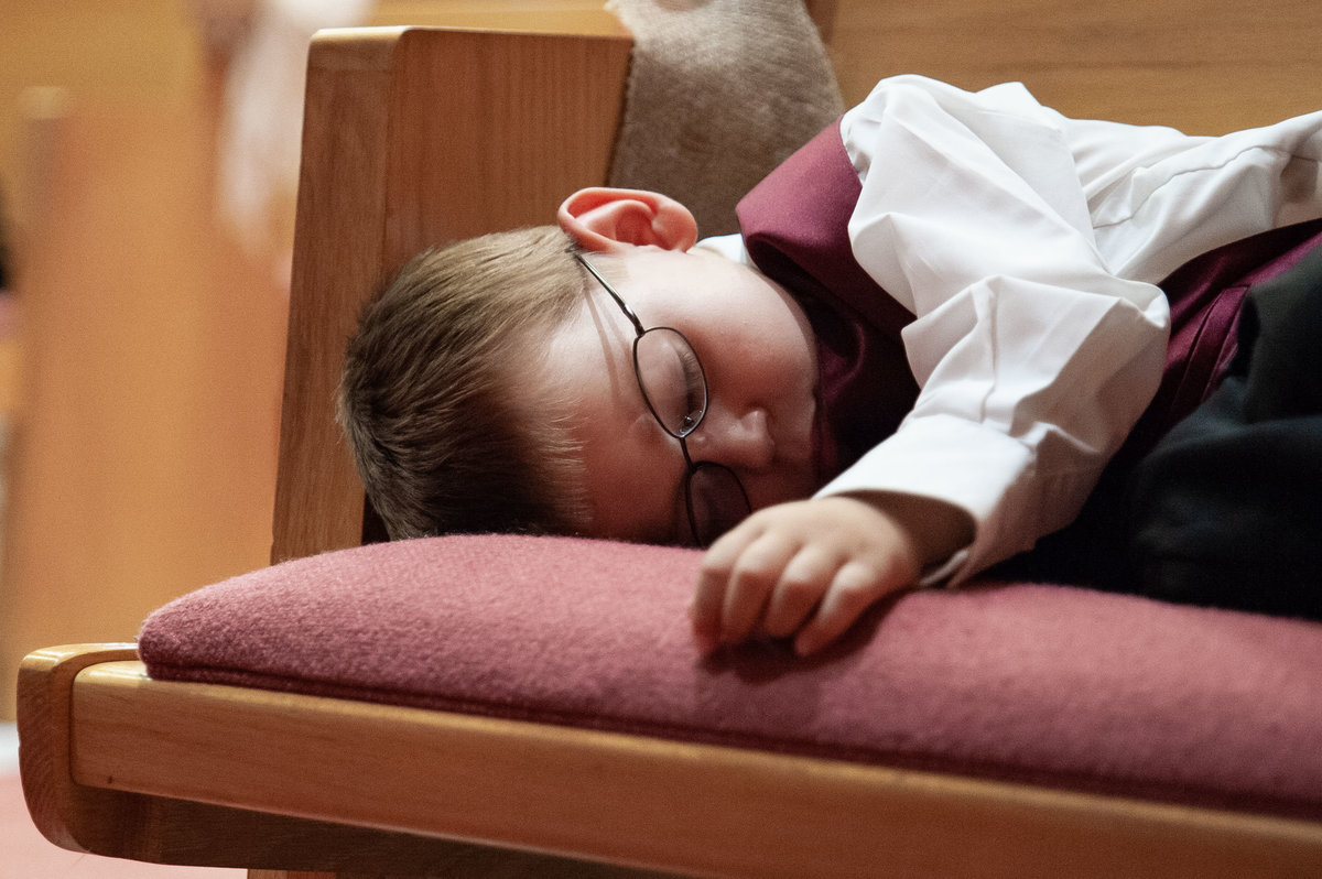 child sleeps on church bench during ceremony