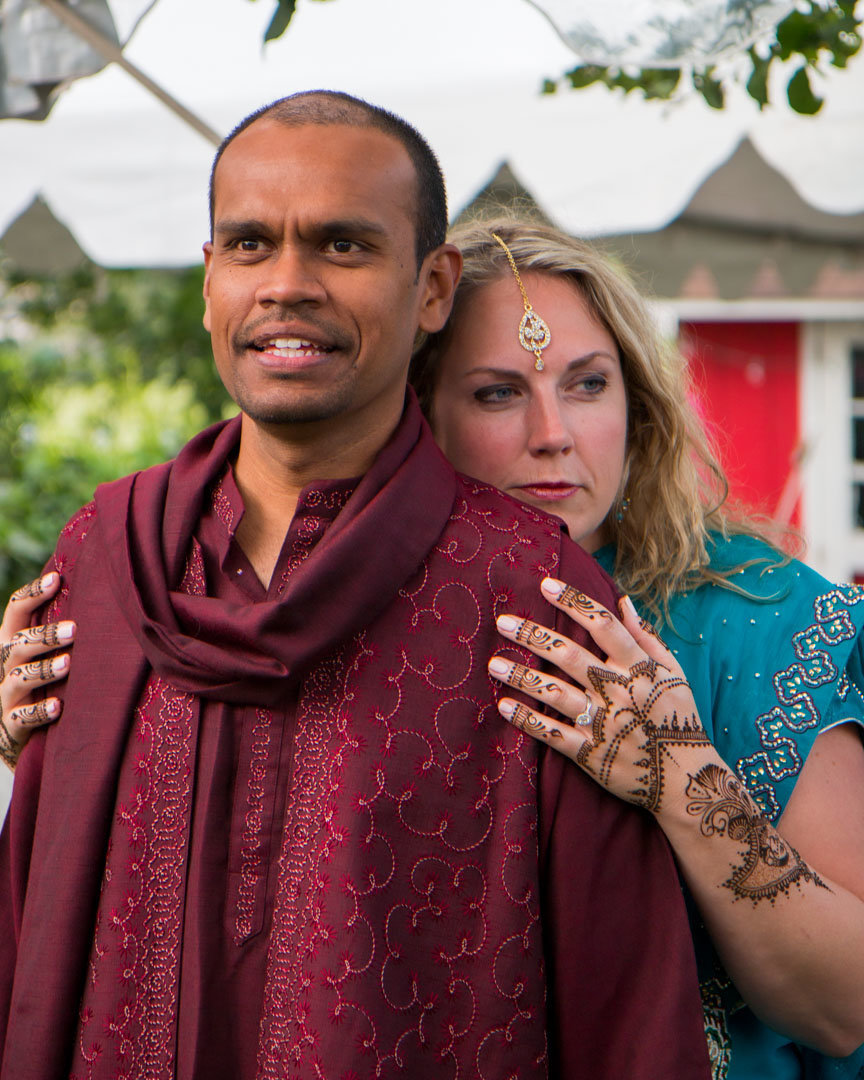 bride holding the shoulders of her groom while she stands behind him and gently rests her cheek against his back with her engagement ring and henna showing on her hand