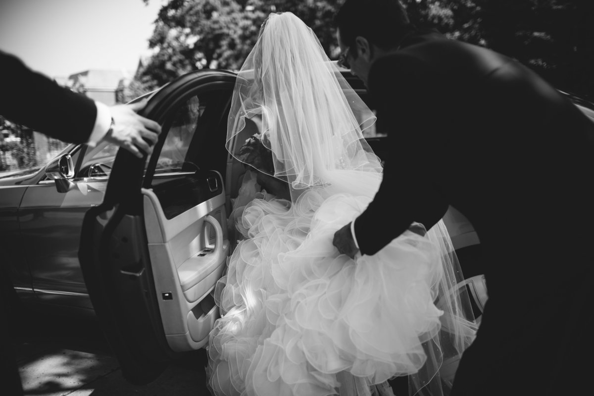 black and white photograph of bride getting into bentley wedding car. she is wearing a big wedding dress