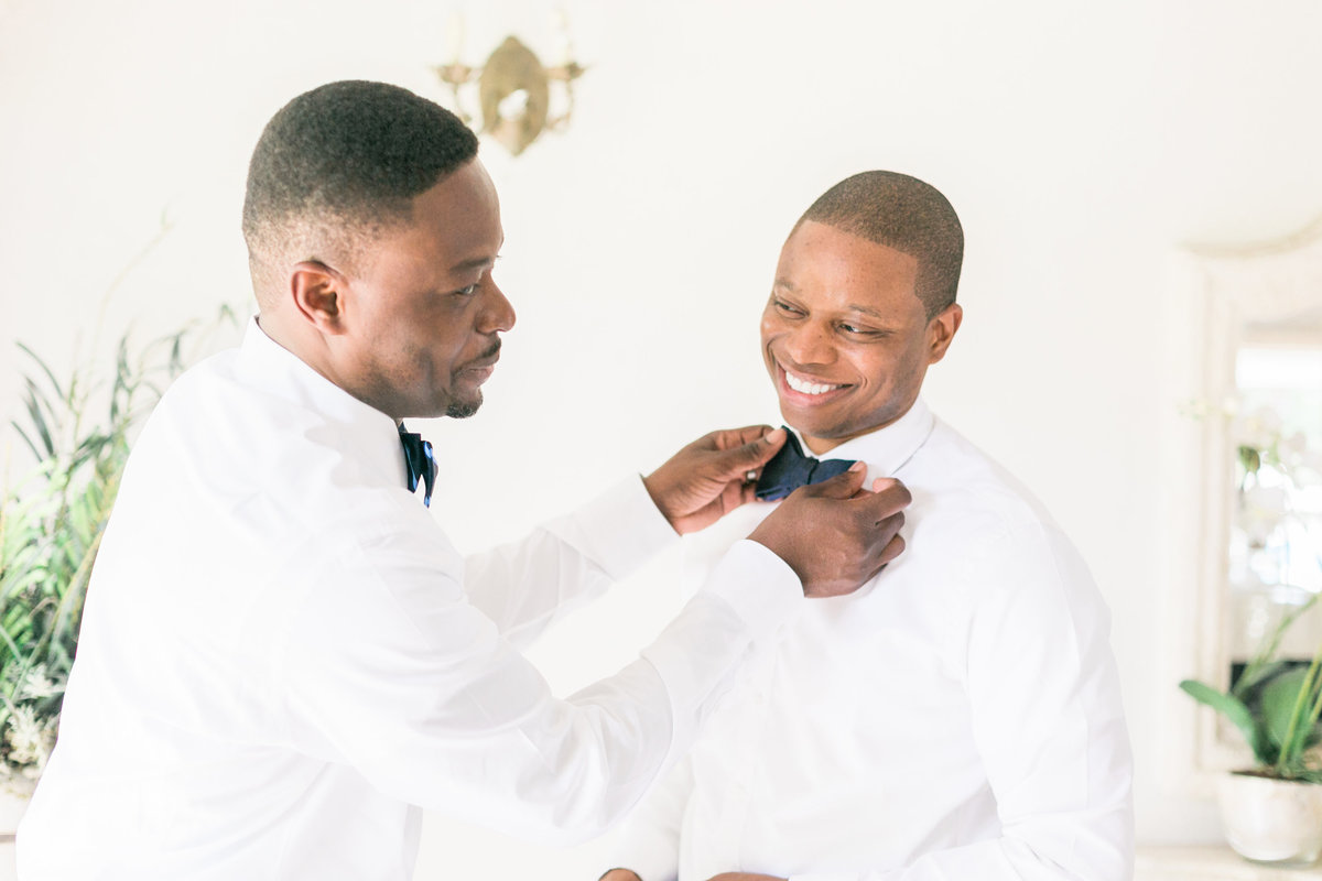 Best Man helping groom with bow tie