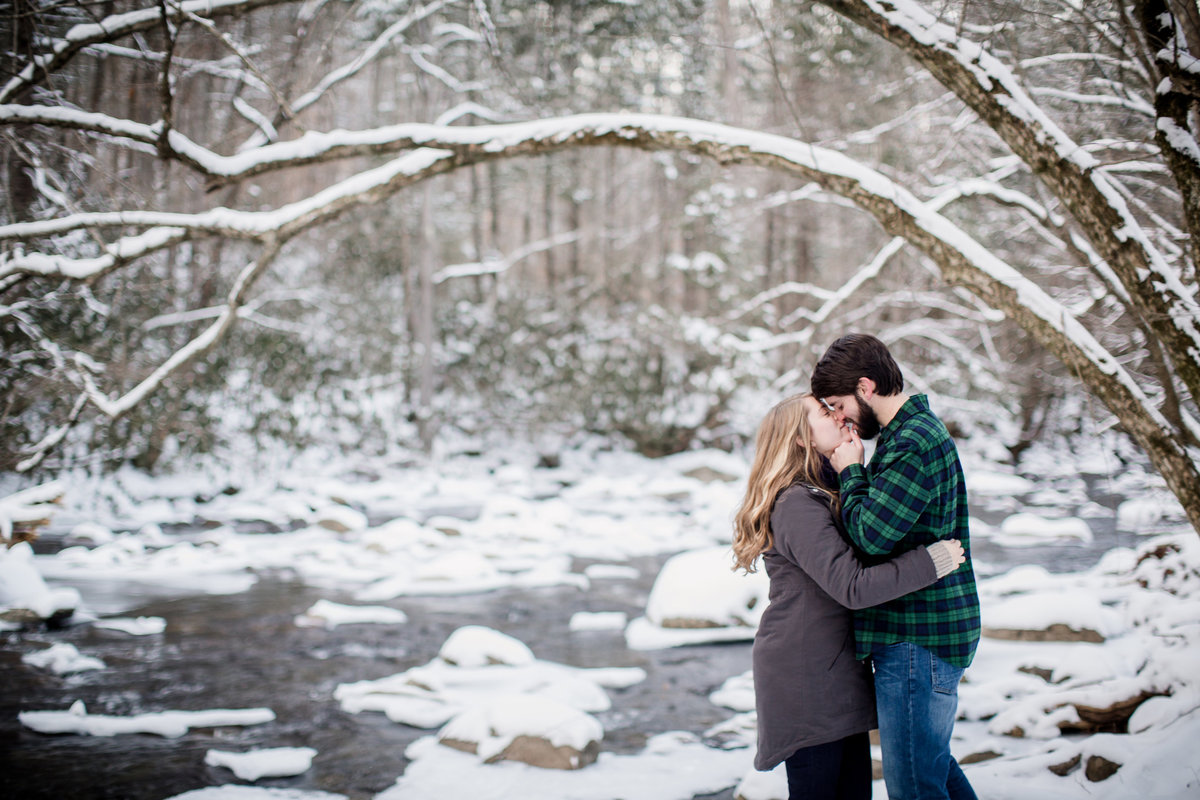 Raising her chin up to kiss her on a snowy day under an arching branch in the Smoky Mountains engagement photo by Knoxville Wedding Photographer, Amanda May Photos.