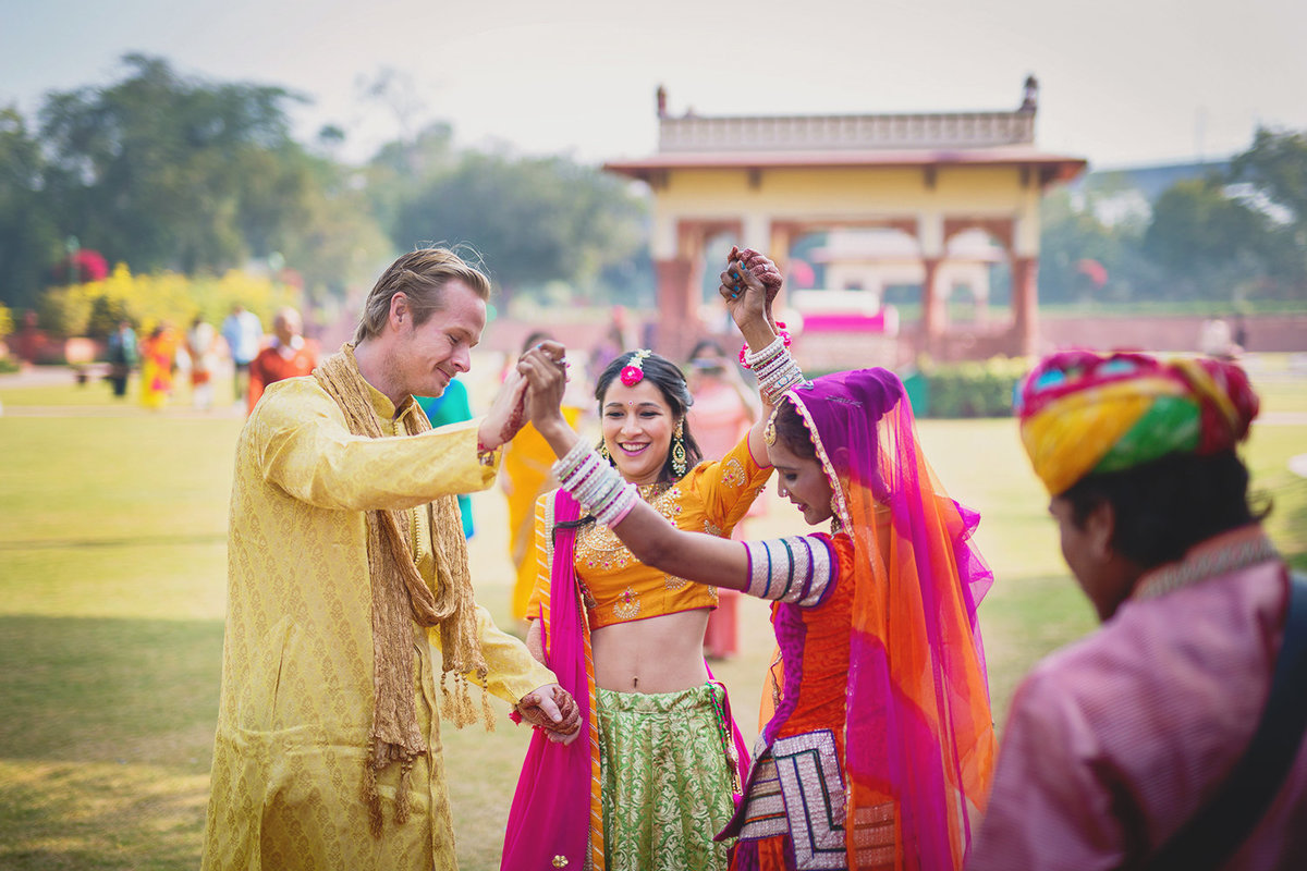 Couple is greeted by folk artists at the Mehendi