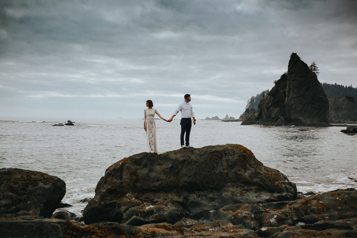 Bride and groom on rocks of La Push Washington in the middle of the Washington coast.