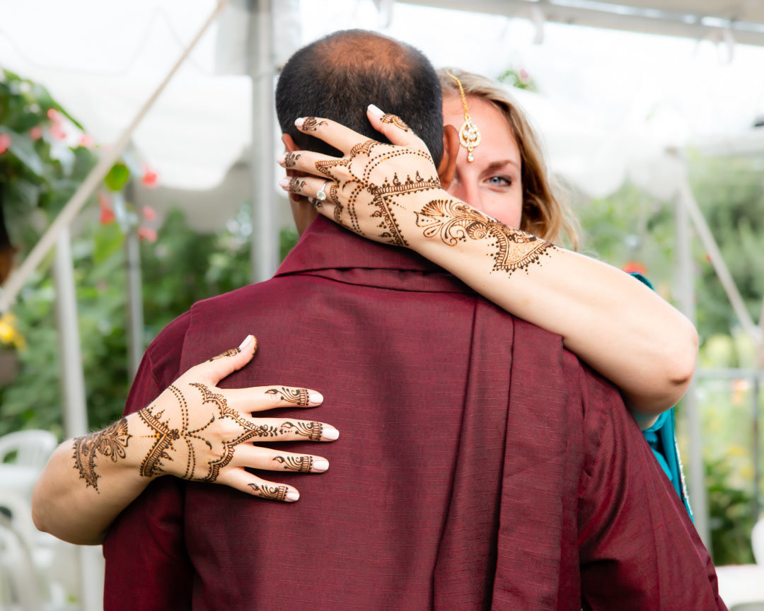 grooms back facing while the bride peers over his shoulder with just one eye showing and her hands on his back with her henna tattoo  designs showing