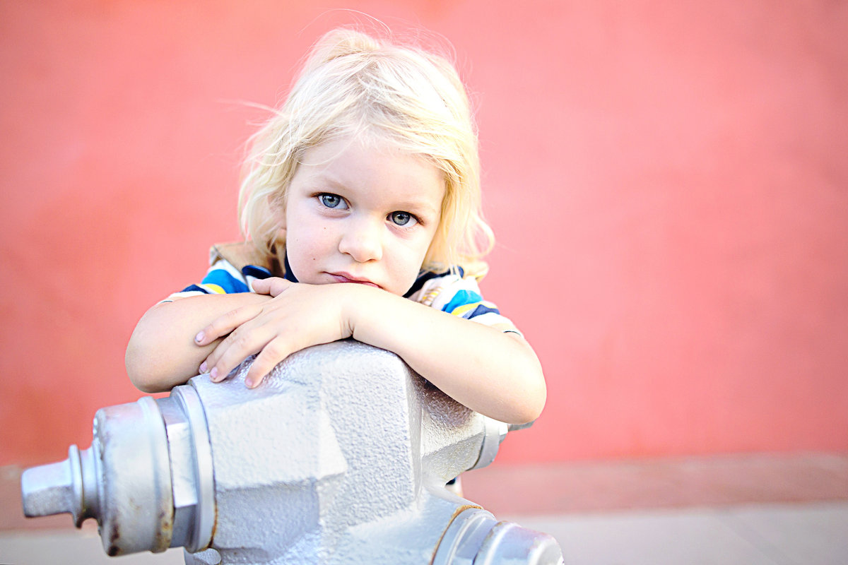 Toddler child stands for a portrait on a fire hydrant