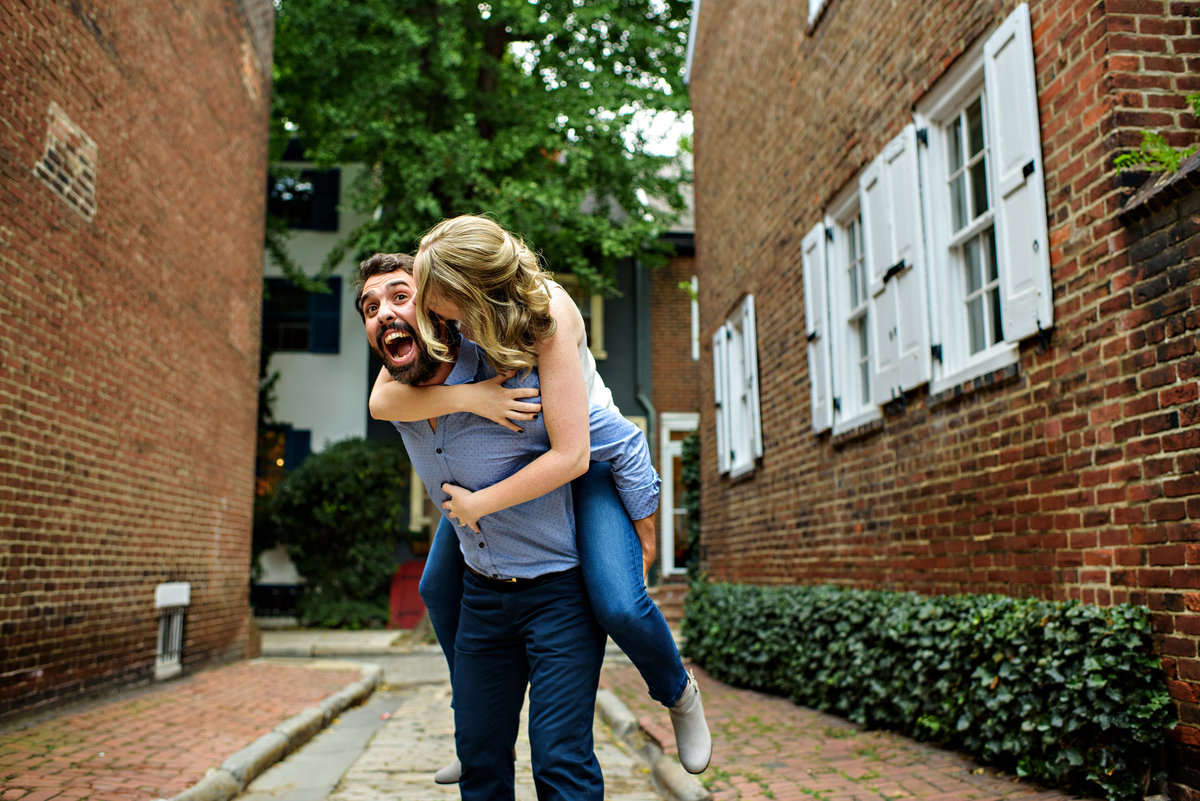 A woman jumps on the back of her fiance during philly engagement session.