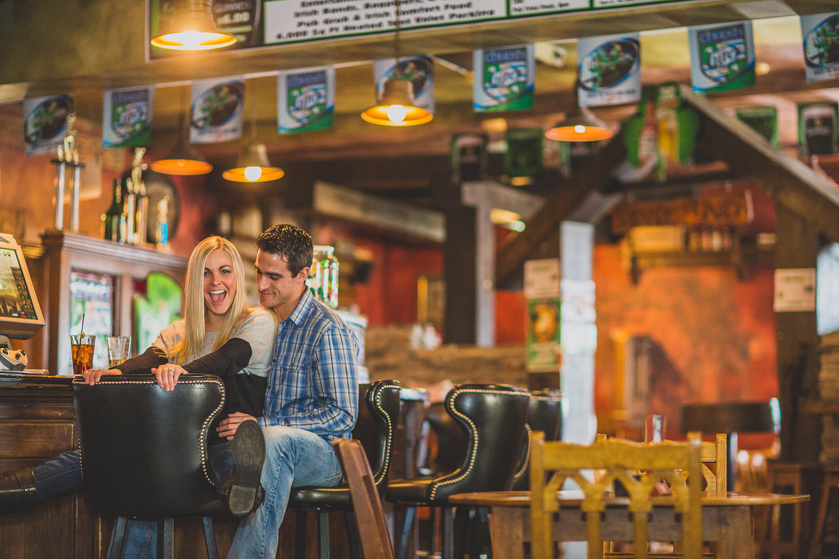 a couple having fun in an irish pub during their engagement photography session