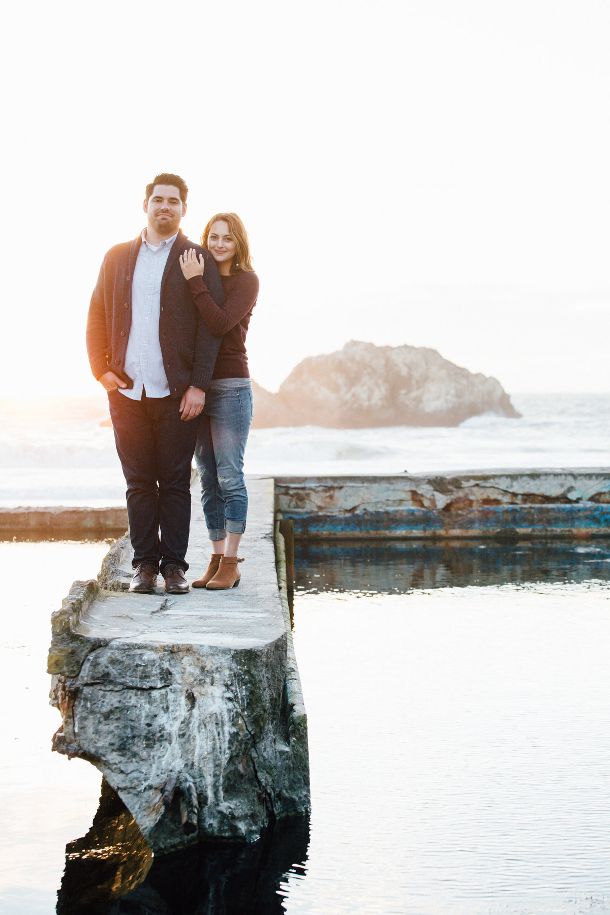 couple poses for engagement photos at golden hour in san francisco