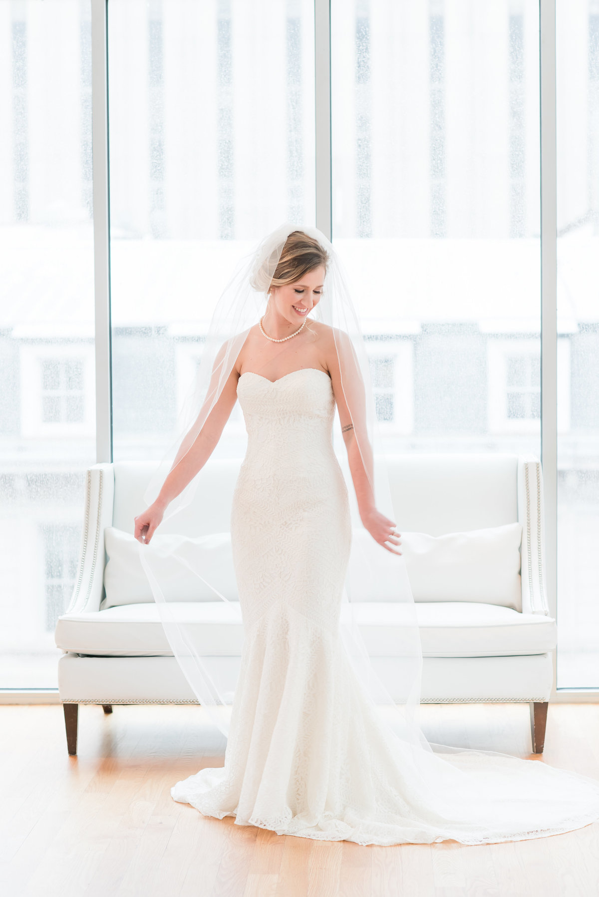 a bride holding her cathedral length veil in Raleigh
