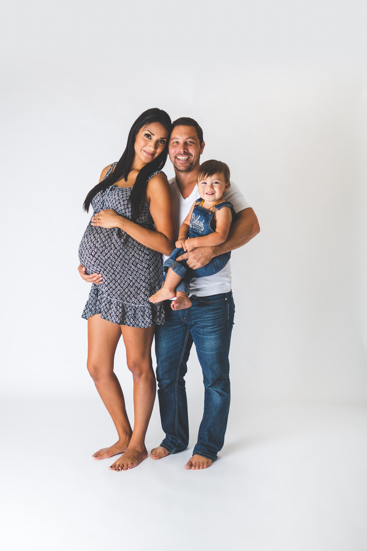 San Antonio In studio family maternity session on a white background with mother holding belly and father holding toddler.