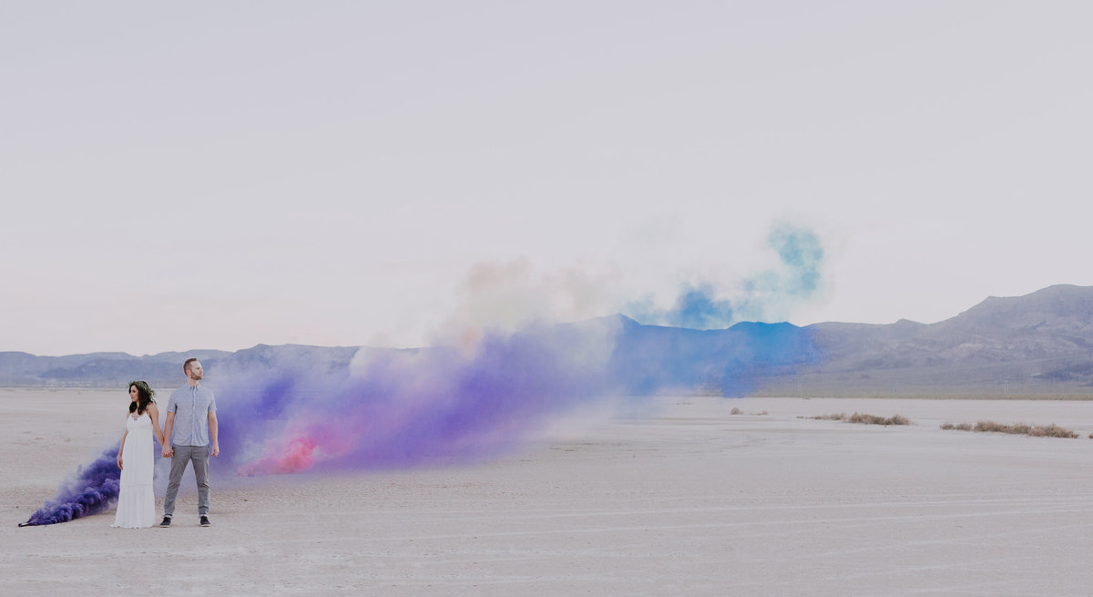 bride and groom pose in desert with smoke bombs
