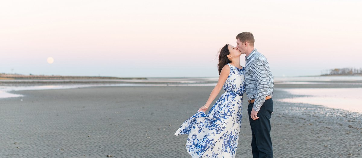 Couple kisses with their reflection in the water and a pink sky at a engagement session at Silver Sands State Park in Milford, Connecticut Photo
