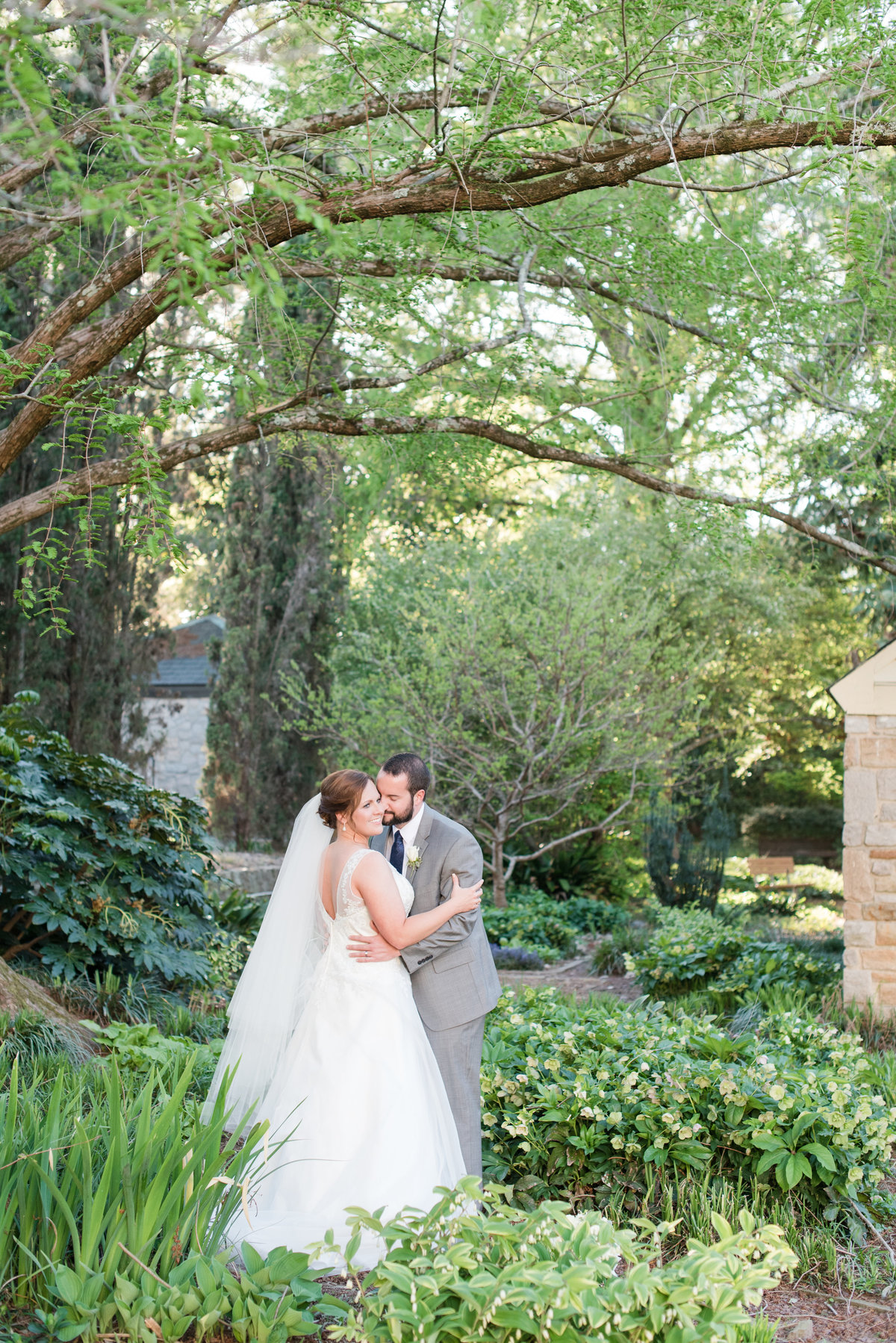 a groom wearing a gray suit kissing the cheek of his bride wearing a laced dress with mid-length veil inside of the Raleigh Rose Garden