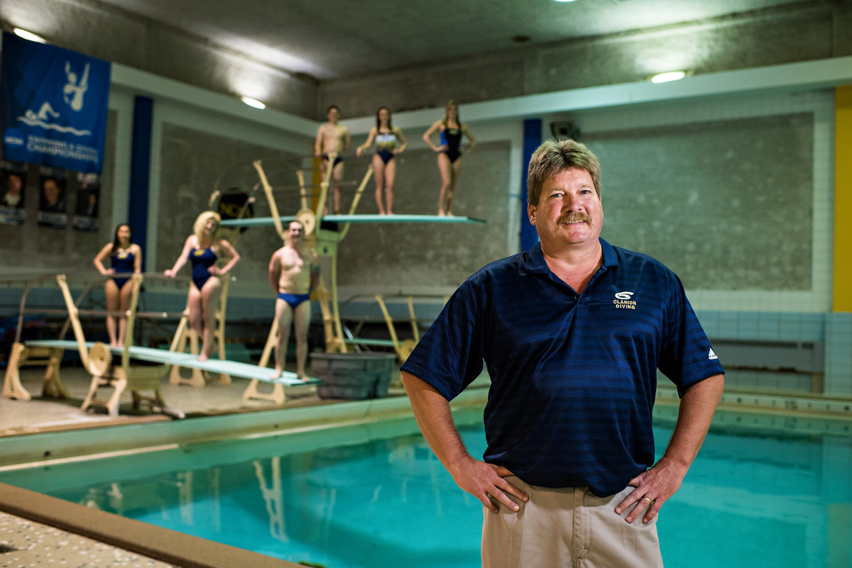 A college swim coach with his students behind him on diving boards.