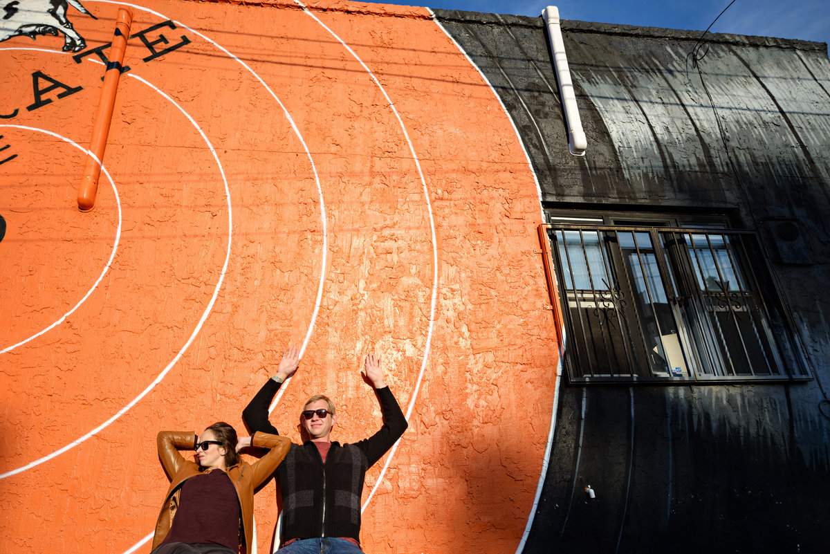 A cool couple leans agains a giant mural of a spinning record on the side of a cafe in Fishtown.