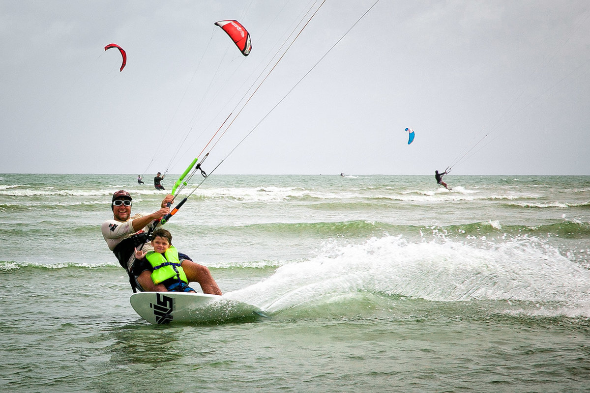 A father and son kite surf leaving a dramatic wake behind them. Photo by Ross Photography, Trinidad, W.I..