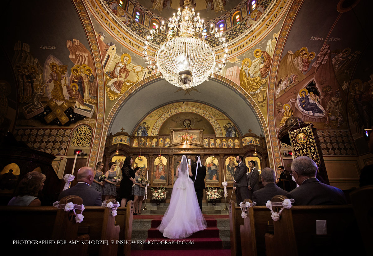 charlotte wedding photographer Jamie Lucido captures a moment during the ceremony with bride and groom at the altar at Holy Trinity Greek Orthodox Church in Charlotte, NC