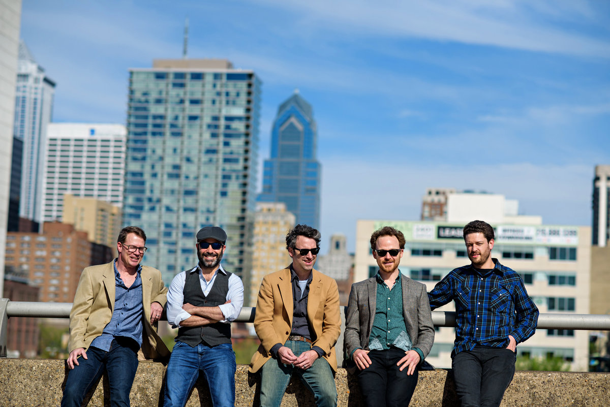 A Philadelphia band called Marc Silver and the Stonethrowers sit on a wall with the philly skyline behind them.