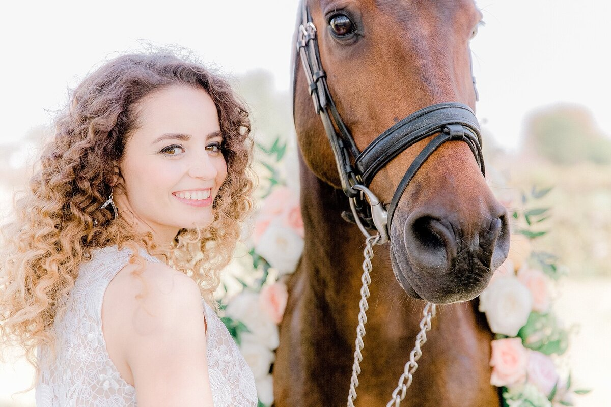 portrait of a bride and her horse who's wearing a floral wreath.