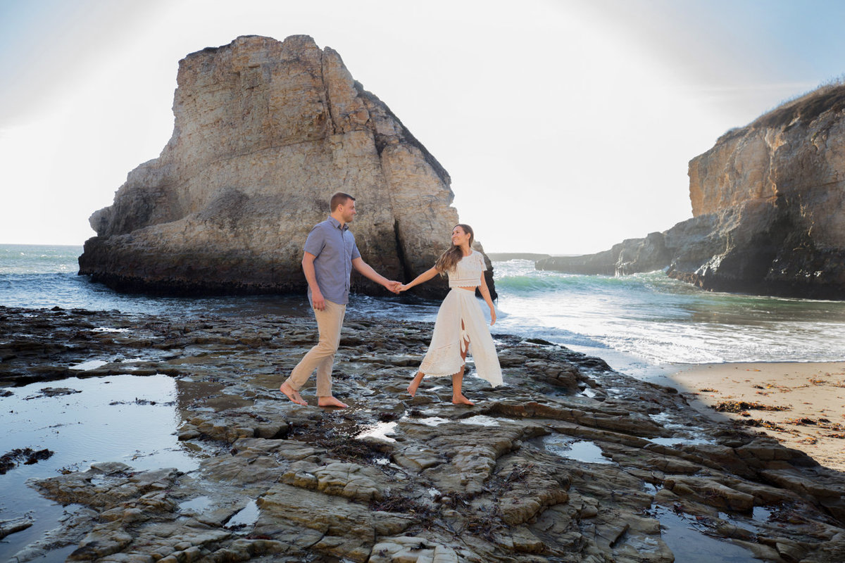 Engagement session on beach, couple holding hands and walking with deneffe studios