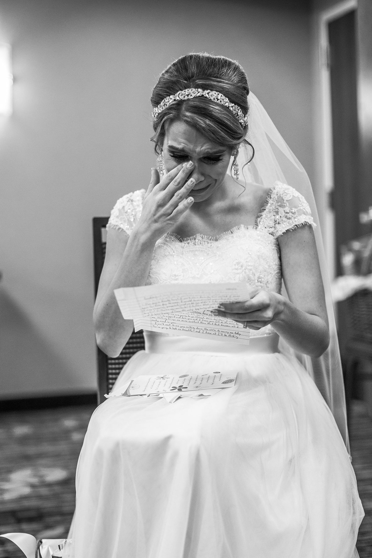 bride reading her note from groom which makes her cry
