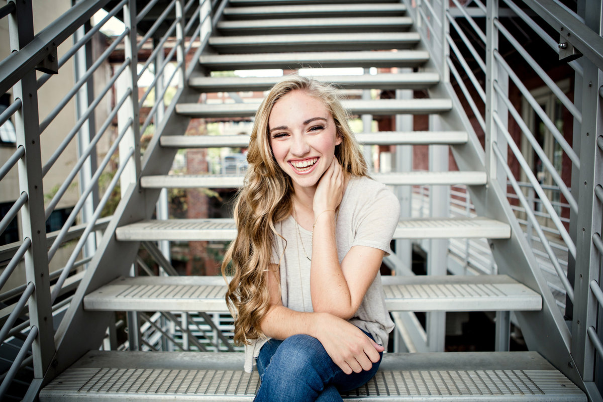 Girl sitting on metal stairs in downtown Knoxville for her senior pictures by Knoxville Wedding Photographer, Amanda May Photos.