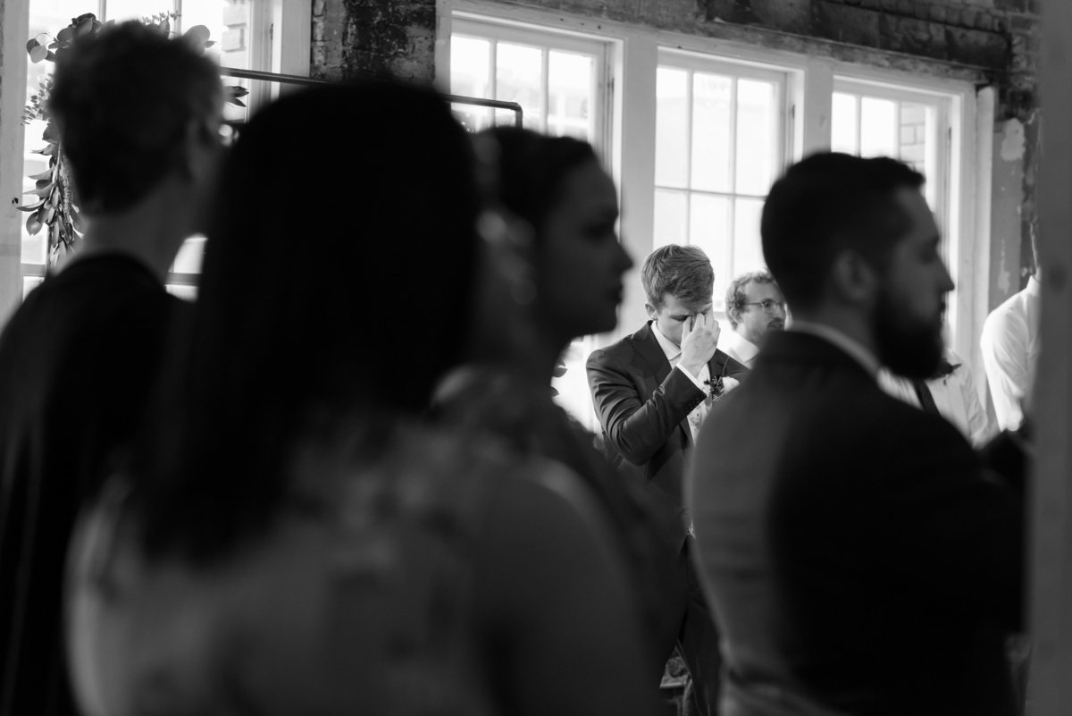 a black and white photograph of a groom holding his face from seeing his bride walk down the aisle for the first time at the Stockroom at 230 in Raleigh