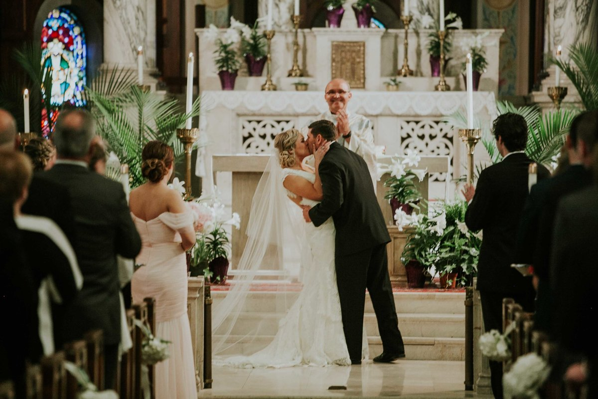 Bride and groom enjoy their first kiss as husband and wife at ST. JOAN OF ARC CATHOLIC CHURCH